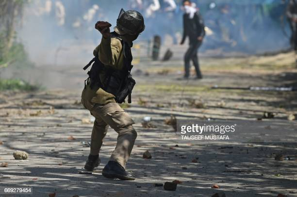 TOPSHOT An Indian government forces throws a stone towards Kashmiri students during clashes near a college in central Srinagar's Lal Chowk on April...