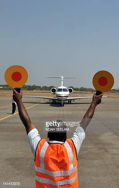 An Indian ground man signals the Hawker 4000 demo flight on the tarmac at the India Aviation2012 show at Begumpet airport in Hyderabad on March 16...