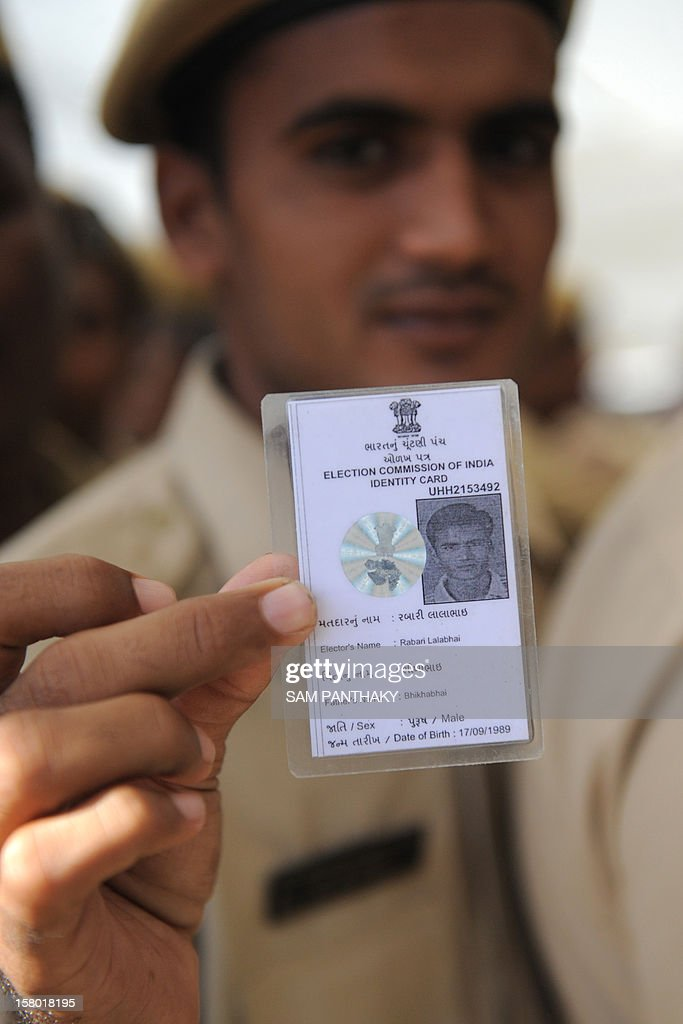 An Indian Gujarat state policeman poses with his voter identity card at the Postal Ballot Issue Centre at the police headquarters in Ahmedabad on December 9, 2012. Large numbers of police officials and homeguards thronged to cast their votes ahead of time by special arrangments made by the election commission for servicemen on duty in the forthcoming Gujarat state elections scheduled for December 13 and 17. AFP PHOTO / Sam PANTHAKY