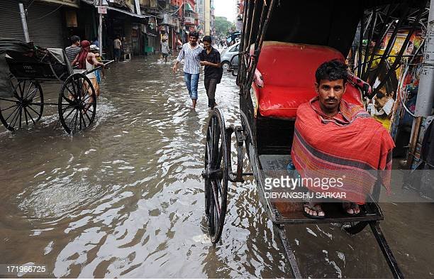 An Indian hand rickshaw puller waits for passengers to ferry along waterlogged streets in Kolkata on June 30 2013 Heavy rains in various parts of...