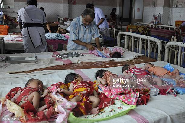 An Indian health official immunises newly born babies inside the maternity ward of a government hospital during World Population Day in Agartala the...