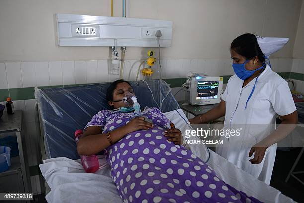 An Indian health professional tends to a patient on a swine flu ward at The Gandhi Hospital in Hyderabad on September 24 2015 Five positive cases of...
