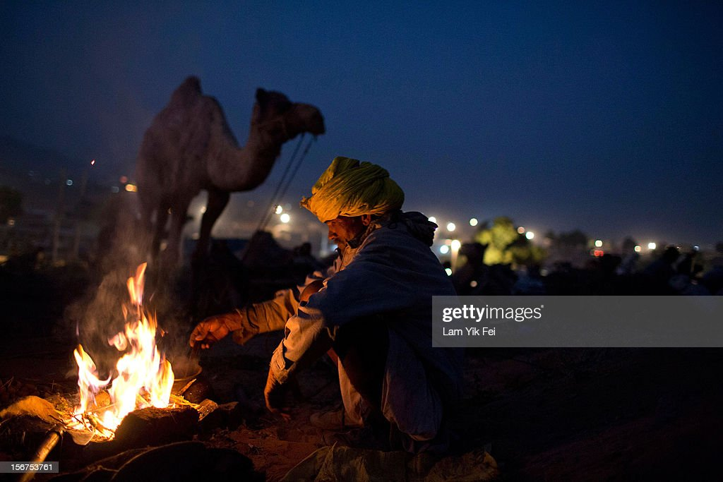 An Indian herder prepares dinner at the end of the day during a camel fair on November 19, 2012 in Pushkar, India. The annual camel and livestock fair is held over five days, and attracts thousands of tourists.