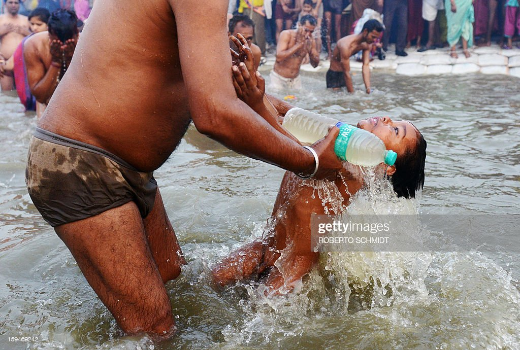 An Indian Hindu boy is dipped into the waters of the Sangham or the confluence of the the Yamuna and Ganges rivers as other devotees pray during the Kumbh Mela in Allahabad on January 14, 2013. Hundreds of thousands of Hindu pilgrims led by naked, ash-covered holy men streamed into the sacred river Ganges at the start of the world's biggest religious festival. The Kumbh Mela in the Indian town of Allahabad will see up to 100 million worshippers gather over the next 55 days to take a ritual bath in the holy waters, believed to cleanse sins and bestow blessings.