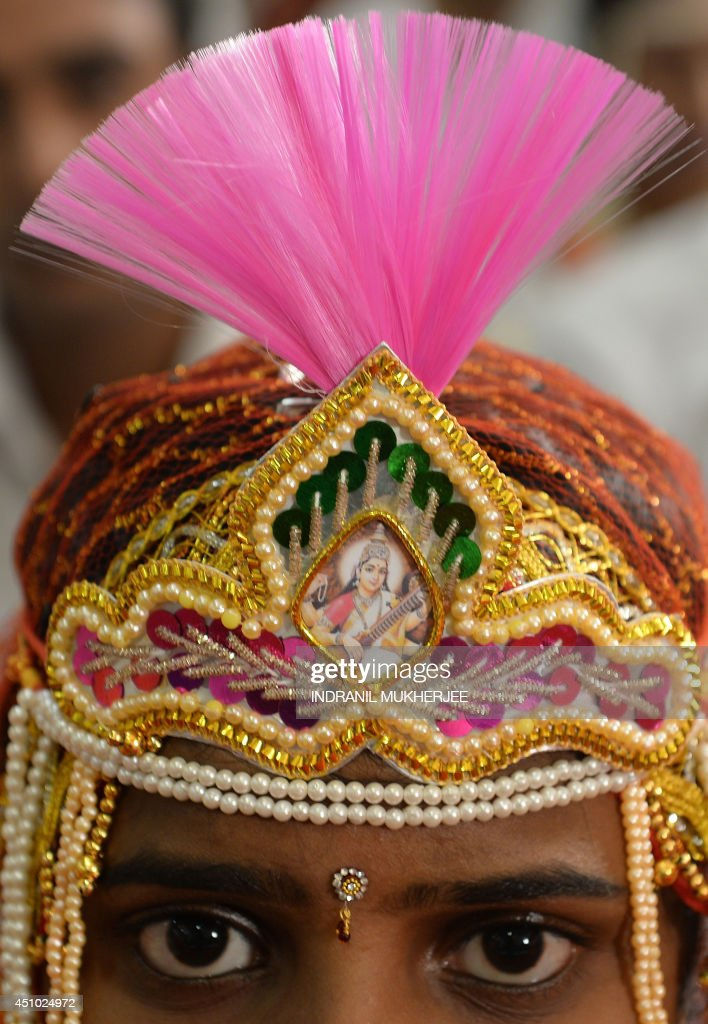 An Indian Hindu bride looks on during a multi-faith mass wedding in Mumbai on June 22, 2014. Over 50 underprivileged couples from different communities were wedded according to the traditions of their faith on the occassion. Mass marriages generally organised by social organisations to cut ceremony costs are common in India with its billion plus population where the custom of dowry and expensive gifts from the bride's family still prevails among certain segments of society.