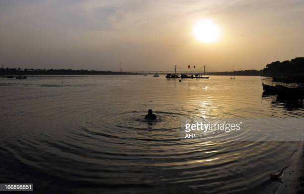 An Indian Hindu devotee bathes at the Sangam the confluence of the rivers Ganges Yamuna and mythical Saraswati in Allahabad on April 18 2013 AFP...