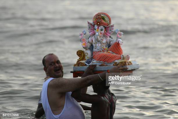 An Indian Hindu devotee carries an idol of the elephantheaded Hindu deity Ganesha for immersion at Dadar Chowpatty beach on the seventh day of the...