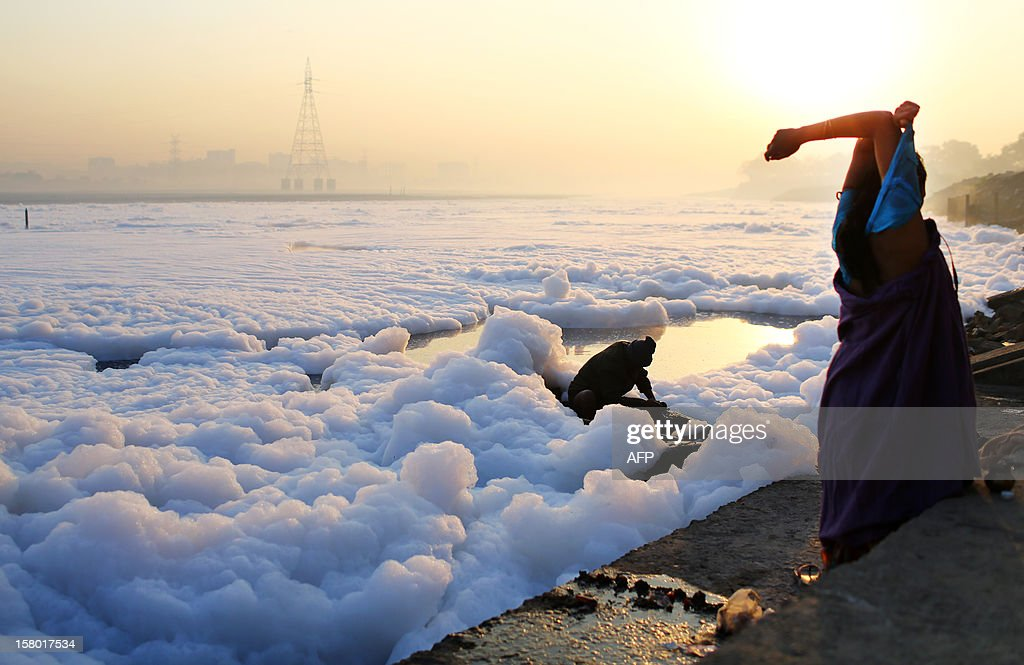 An Indian Hindu devotee (R) changes as a boatman bails water from his boat amid polluted foam in the Yamuna river in New Delhi on December 9, 2012. India's Supreme Court said on December 8, all parameters of water quality of river Yamuna indicate that it resembles a drain and urged authorities to make it pollution-free. Over 2,400 million liters of untreated sewage flows into the Yamuna every day. AFP PHOTO/ Andrew Caballero-Reynolds