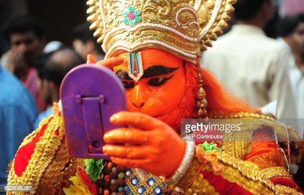 An Indian Hindu devotee dressed as the monkey god Hanuman prepares for a procession for the Hindu festival Hanuman Jayanti in Allahabad on October 18...