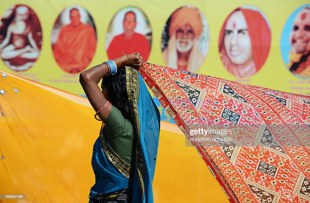 An Indian Hindu devotee dries her sari in the wind as she stands near a billboard showing Hindu Gurus near a street in the sprawling grounds of the Maha Kumbh Mela festival in Allahabad on February 8, 2013. The Kumbh Mela in the town of Allahabad will see up to 100 million worshippers gather over 55 days to take a ritual bath in the holy waters, believed to cleanse sins and bestow blessings.