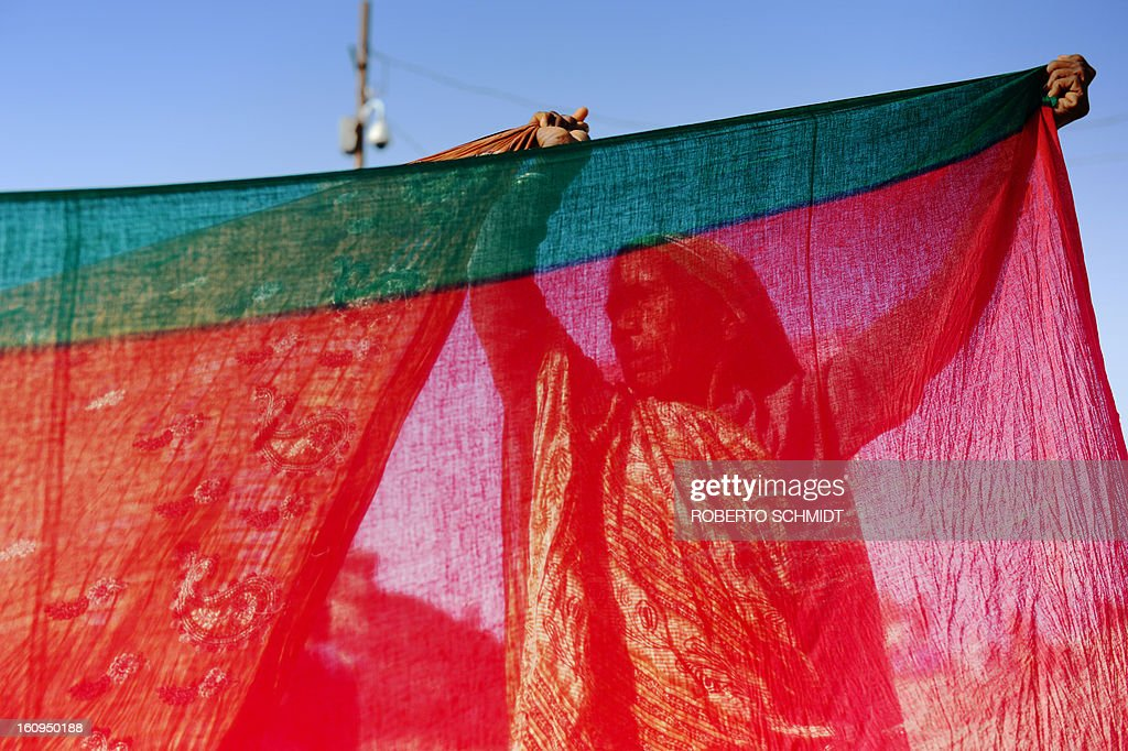 An Indian Hindu devotee dries saris after bathing in the confluence of the Yamuna and Ganges river during the Maha Kumbh Mela festival in Allahabad on February 8, 2013. The Kumbh Mela in the town of Allahabad will see up to 100 million worshippers gather over 55 days to take a ritual bath in the holy waters, believed to cleanse sins and bestow blessings.