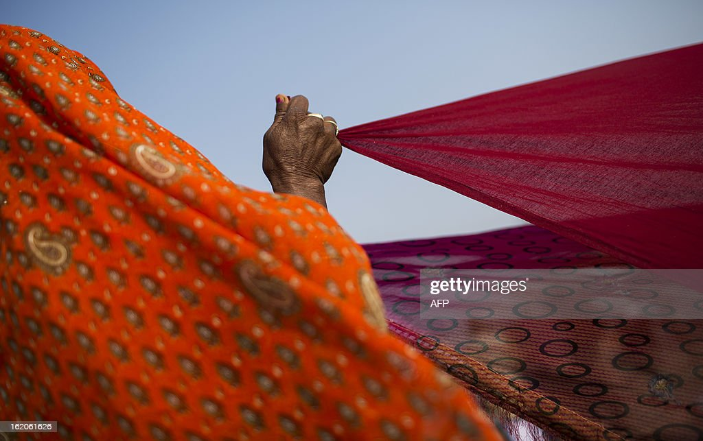 An Indian Hindu devotee dries saris near the Sangam or confluence of the Yamuna, Ganges and mythical Saraswati rivers at the Kumbh Mela in Allahabad on February 19, 2013. The Kumbh Mela in the town of Allahabad will see up to 100 million worshippers gather over 55 days to take a ritual bath in the holy waters, believed to cleanse sins and bestow blessings. AFP PHOTO/ Andrew Caballero-Reynolds