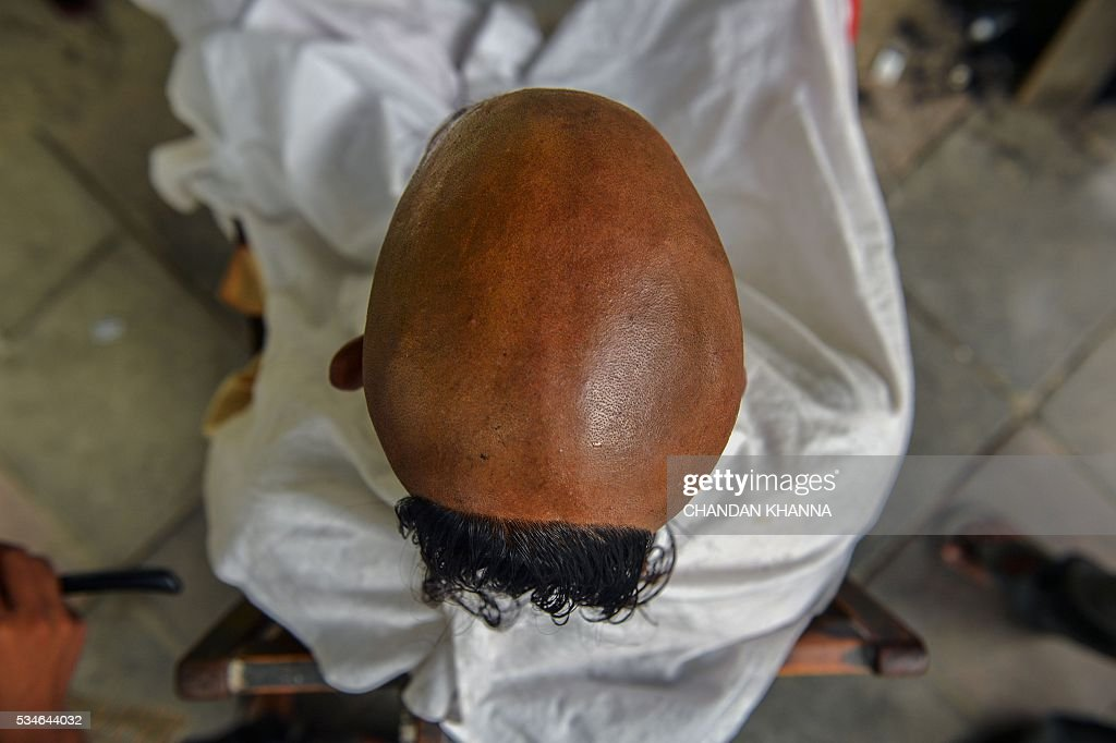 An Indian Hindu devotee gets his hair cut at a roadside barber shop in New Delhi on May 27, 2016. / AFP / CHANDAN