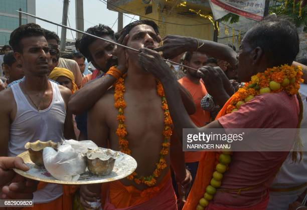An Indian Hindu devotee has his cheeks pierced wih an iron rod by a priest while taking part in a procession to honour the Hindu goddess Maha...