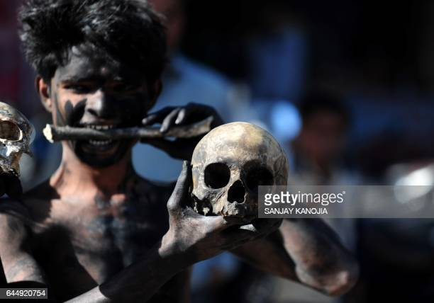 TOPSHOT An Indian Hindu devotee holds a human skull and bone during a procession for Maha Shivaratri dedicated to the Hindu god Lord Shiva in...