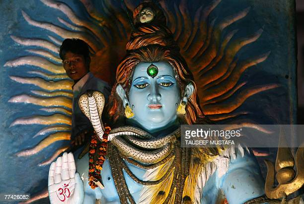 An Indian Hindu devotee looks out from behind an idol of Hindu God Lord Shiva during a religious procession on the eve of the Hindu festival of...