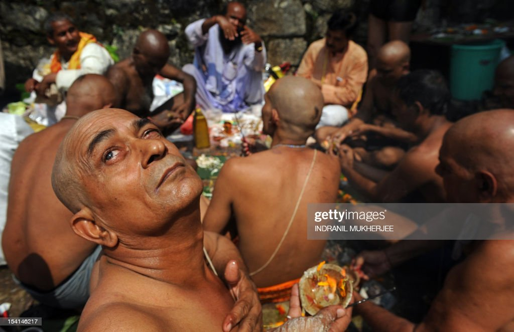 An Indian Hindu devotee looks up skyward as he and others perform 'Tarpan', a ritual to pay obesience to one's forefathers, on the last day for offering prayers to ancestors called 'Pitrupaksh' in Mumbai on October 15, 2011. In Hindu mythology, this day is also called 'Mahalaya' and described as the day when the gods created the ten armed goddess Durga to destroy the demon king Asura who plotted to drive out the gods from their kingdom. The five-day period of worship of Durga, who is attributed as the destroyer of evil, commences on October 20. AFP PHOTO/Indranil MUKHERJEE