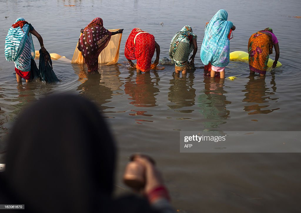 An Indian Hindu devotee (foreground L) makes an offering as other women wash their saris at the Sangam or confluence of the Yamuna, Ganges and mythical Saraswati rivers at the Kumbh Mela in Allahabad on February 19, 2013. The Kumbh Mela in the town of Allahabad will see up to 100 million worshippers gather over 55 days to take a ritual bath in the holy waters, believed to cleanse sins and bestow blessings. AFP PHOTO/ Andrew Caballero-Reynolds