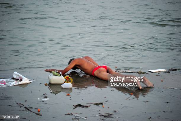 An Indian Hindu devotee performs a ritual before taking a holy dip at Sangam the confluence of the three great rivers Ganga Yamuna and the mystical...