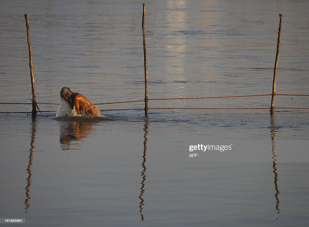 An Indian Hindu devotee performs rituals as he bathes in the river on February 17, 2013 during the Kumbh Mela festival in Allahabad. The Kumbh Mela in the town of Allahabad will see up to 100 million worshippers gather over 55 days to take a ritual bath in the holy waters, believed to cleanse sins and bestow blessings. The Kumbh Mela, which ends in March, takes place every 12 years in Allahabad. AFP PHOTO / Andrew Caballero-Reynolds