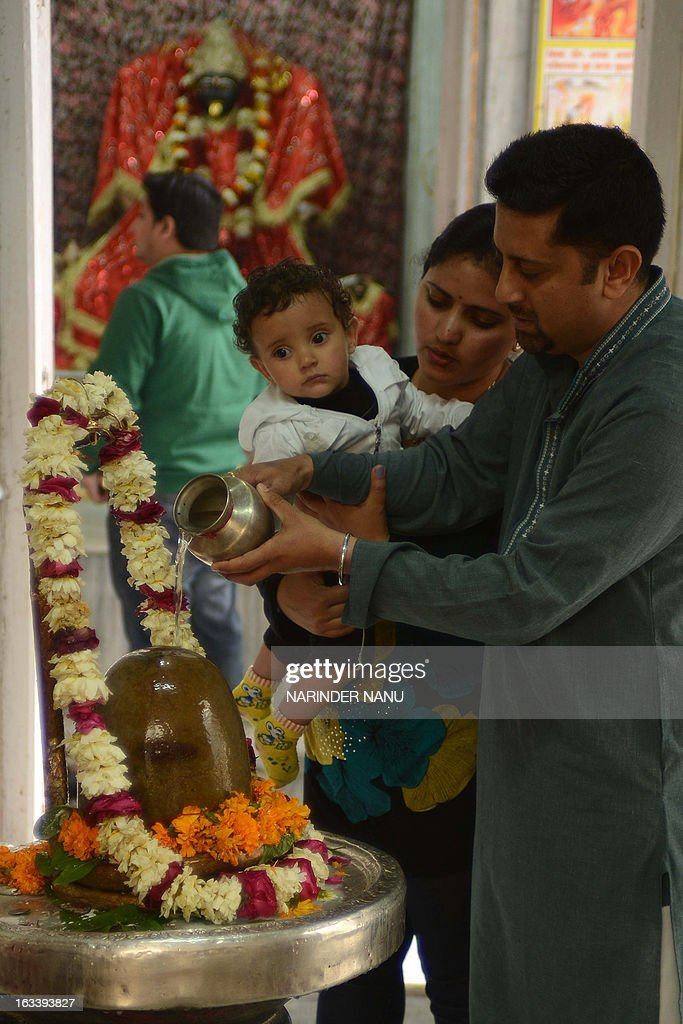 An Indian Hindu devotee pours milk over a Shivling or idol of Lord Shiva at a temple in Amritsar on March 9, 2013 on the eve of Maha Shivratri festival. Hindus mark the Maha Shivratri festival by offering special prayers and fasting to worship Lord Shiva, the lord of destruction.