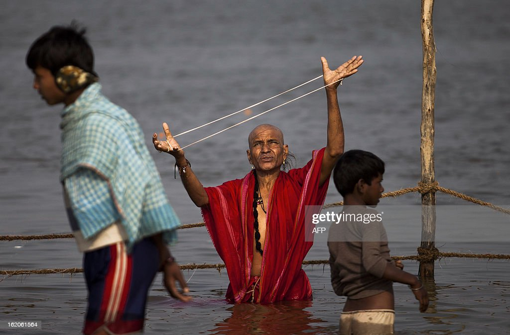 An Indian Hindu devotee prays in the Sangam or confluence of the Yamuna, Ganges and mythical Saraswati rivers at the Kumbh Mela in Allahabad on February 19, 2013. The Kumbh Mela in the town of Allahabad will see up to 100 million worshippers gather over 55 days to take a ritual bath in the holy waters, believed to cleanse sins and bestow blessings. AFP PHOTO/ Andrew Caballero-Reynolds