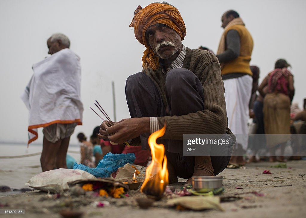 An Indian Hindu devotee prepares offerings at the Sangam or confluence of the Yamuna, Ganges and mythical Saraswati rivers at the Kumbh Mela in Allahabad on February 17, 2013. The Kumbh Mela in the town of Allahabad will see up to 100 million worshippers gather over 55 days to take a ritual bath in the holy waters, believed to cleanse sins and bestow blessings. AFP PHOTO/ Andrew Caballero-Reynolds