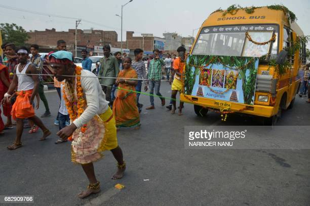 An Indian Hindu devotee pulls a van attached to steel piercings through his back while taking part in a procession to honour the Hindu goddess Maha...
