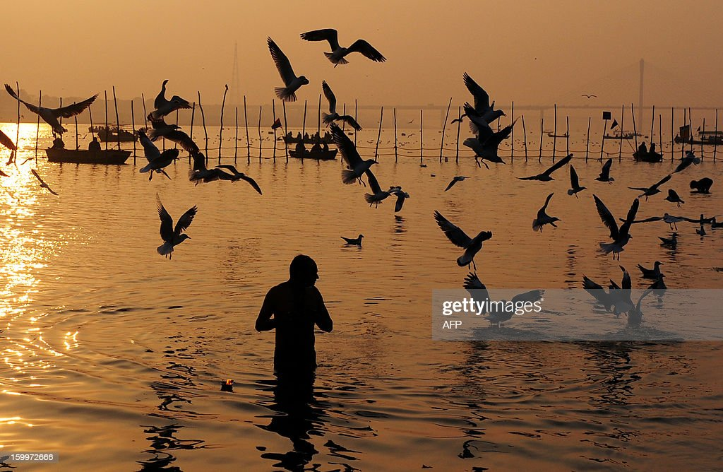 An Indian Hindu devotee takes a dip in the Sangam, the confluence of the rivers Ganges and Yamuna in Allahabad on January 24, 2013. The Kumbh Mela in the Indian town of Allahabad will see up to 100 million worshippers gather over the next 55 days to take a ritual bath in the holy waters, believed to cleanse sins and bestow blessings. AFP PHOTO/ Sanjay KANOJIA