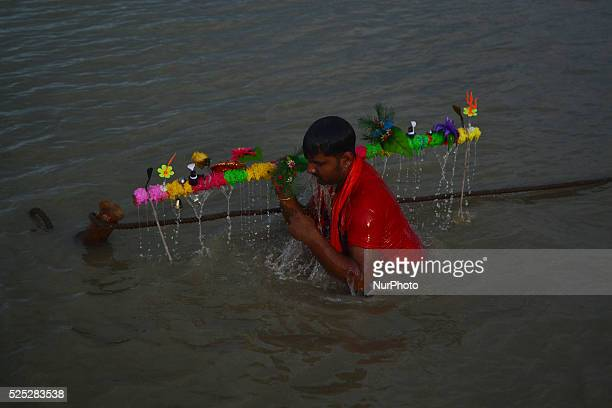 An Indian hindu devotee takes a holy dip in River Ganga before starting his kanwar yatra on the sacred month of Shravan at Daraganj Ghat in Allahabad...