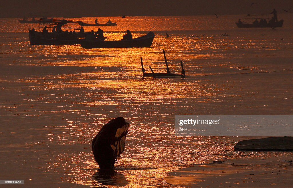 """An Indian Hindu devotee takes a holy dip in the 'Sangam,"""" the confluence of the three rivers Ganges, Yamuna and mythical Saraswati in Allahabad on December 22, 2012, ahead of the Mahakumbh Mela. The Kumbh Mela, which is scheduled to take place in the northern Indian city in January and February 2013, is the world's largest gathering of people for a religious purpose and millions of people gather for this auspicious occasion. AFP PHOTO/ Sanjay KANOJIA"""