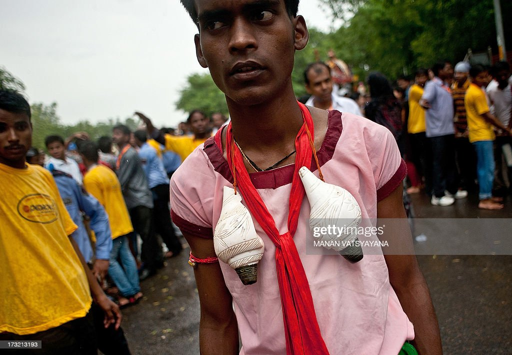 An Indian Hindu devotee wears a pair of conch-shells around his neck during Lord Jagannath's Rath Yatra celebrations in New Delhi on July 10, 2013. This year marks the 136th annual Rath Yatra, where wooden images or idols of Lord Jagannath, his brother Balabhadra and sister Subhadra are mounted on ceremonial chariots and taken out in a procession with the participation of thousands of devotees.