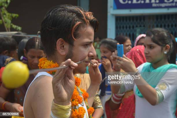 An Indian Hindu devotee with steel rod piercings through his cheeks walks while taking part in a procession to honour the Hindu goddess Maha...