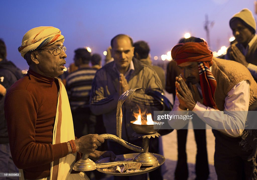 An Indian Hindu holy man gives blessings to devotees after evening prayers on February 17, 2013 during the Kumbh Mela festival in Allahabad. The Kumbh Mela in the town of Allahabad will see up to 100 million worshippers gather over 55 days to take a ritual bath in the holy waters, believed to cleanse sins and bestow blessings. The Kumbh Mela, which ends in March, takes place every 12 years in Allahabad. AFP PHOTO / Andrew Caballero-Reynolds