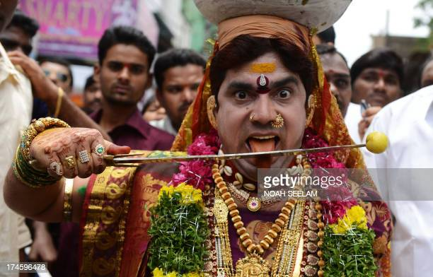 An Indian Hindu male devotee dressed as a women carries 'ghatam' a pot filled with cooked rice and decorated with neem leaves during the festival of...