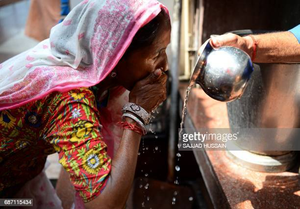 TOPSHOT An Indian Hindu man pours drinking water for a woman outside a temple amid rising temperatures in New Delhi on May 23 2017 Temperatures in...