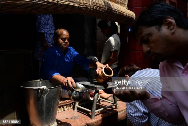 An Indian Hindu man pours drinking water for pedestrians outside a temple amid rising temperatures in New Delhi on May 23 2017 Temperatures in the...