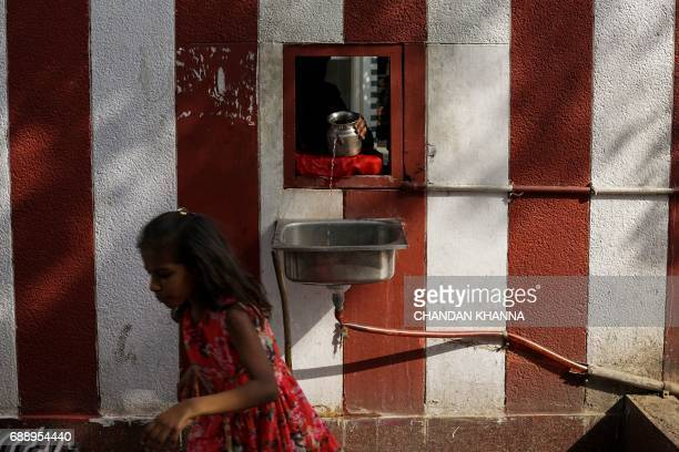 An Indian Hindu man pours drinking water for pedestrians outside a temple amid rising temperatures in New Delhi on May 27 2017 Temperatures in the...