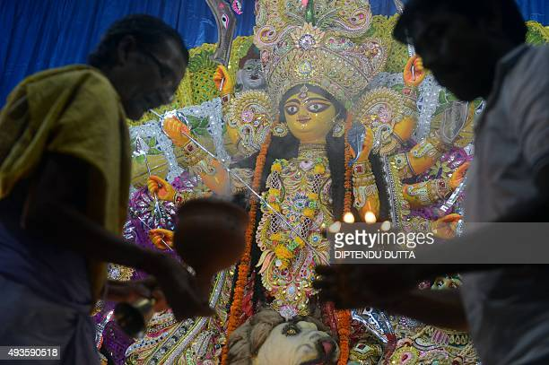 An Indian Hindu priest and a devotee offer evening prayer in front of an idol of the Goddess Durga in Siliguri on October 21 2015The Hindu Festival...
