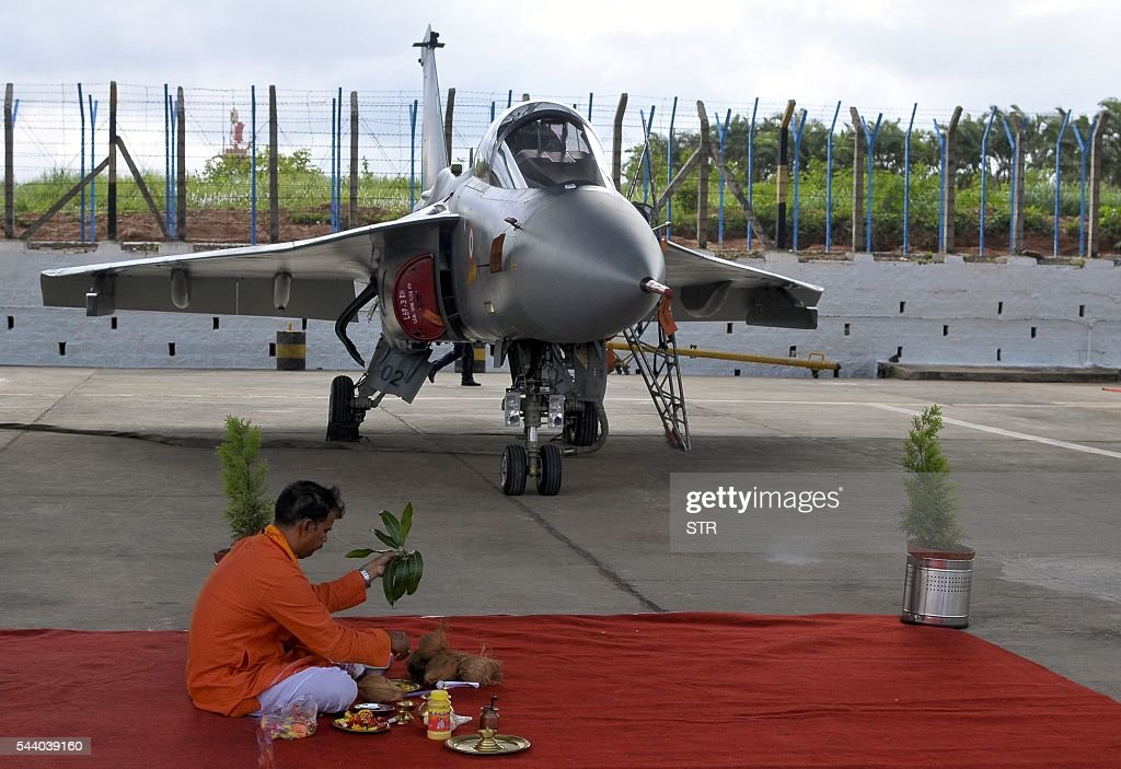 An Indian Hindu priest conducts a ritual in fromt of a newly commissioned Indian Air Force (IAF) Tejas or Light Combat Aircraft (LCA) in Bangalore on July 1, 2016, during a ceremony in the southern Indian city. India's air force added its first domestically developed light fighter aircraft to its fleet, as it phases out ageing Russian jets dubbed 'Flying Coffins'. The bellow of conch shells and crack of breaking coconuts -- auspicious Hindu rituals -- sounded as the two Tejas jets were handed over to the Indian Air Force in the southern city of Bangalore. / AFP / STR