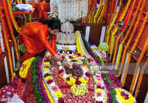 An Indian Hindu priest decorates a statue of the Hindu monkey god Hanuman during for Hanuman Jayanti at the Bade Hanuman temple near Sangam in...
