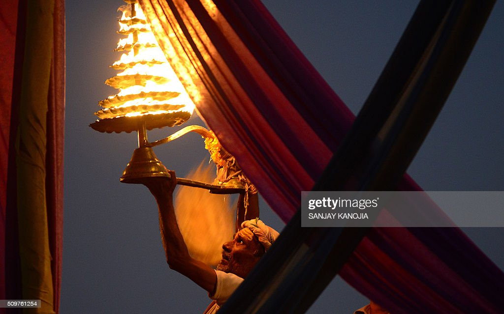 An Indian Hindu priest perform Arti evening prayers on the banks of the River Ganges during the annual Magh Mela festival in Allahabad on February 12, 2016. AFP PHOTO / SANJAY KANOJIA / AFP / Sanjay Kanojia
