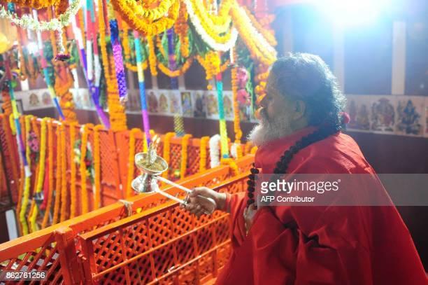 An Indian Hindu priest performs an Arti offering for Hanuman Jayanti at the Bade Hanuman temple near Sangam in Allahabad on October 18 2017 Hanuman...