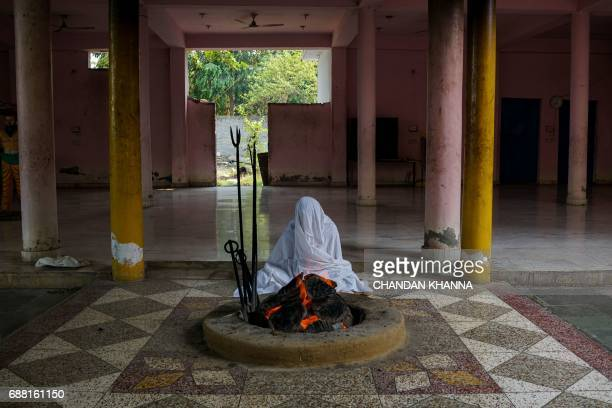 An Indian Hindu priest prays next to a fire inside a temple in New Delhi on May 25 2017 / AFP PHOTO / CHANDAN KHANNA
