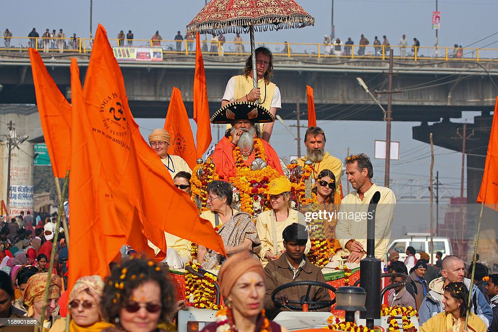 An Indian Hindu Saddhu (C), accompanied caucasian devotees, participate in a religion procession as the first 'royal entry' for the Kumbh Mela at Sangam in Allahabad on January 3, 2013. The Kumbh Mela, which is scheduled to take place in the northern Indian city in January and February 2013, is the world's largest gathering of people for a religious purpose and millions of people gather for this auspicious occasion. AFP PHOTO/ Sanjay KANOJIA