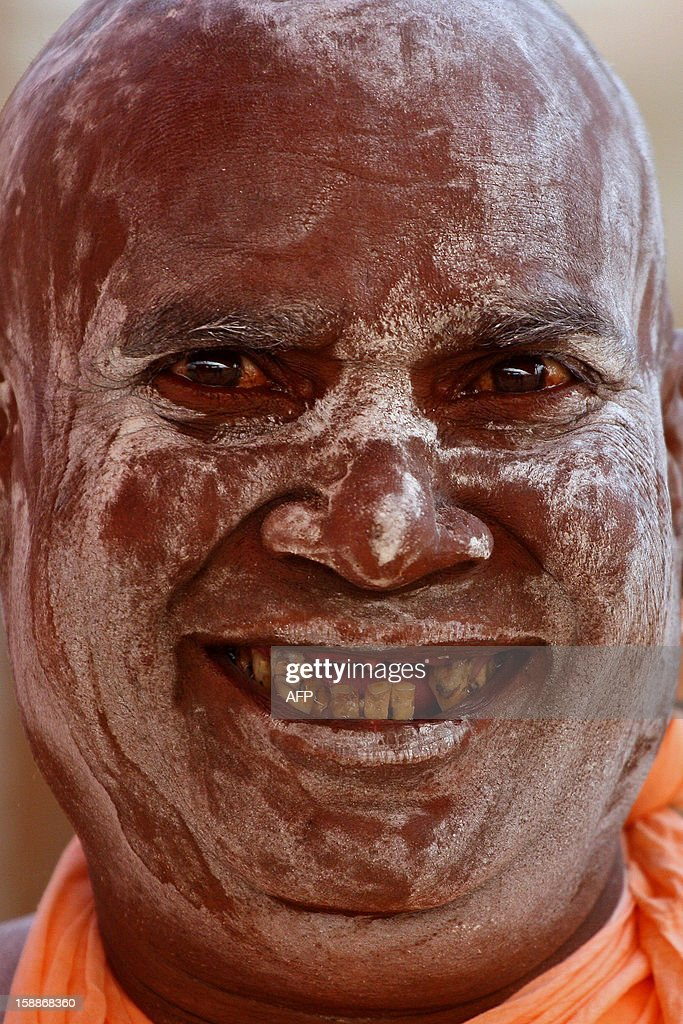 An Indian Hindu Saddhu (holy man) - his face smeared with ash - smiles for a photograph at the confluence of the Rivers Ganges, Yamuna and mythical Saraswati in Allahabad on January 2, 2013, ahead of The Maha Kumbh Mela. The Kumbh Mela, which is scheduled to take place in the northern Indian city in January and February 2013, is the world's largest gathering of people for a religious purpose and millions of people gather for this auspicious occasion. AFP PHOTO/ Sanjay KANOJIA