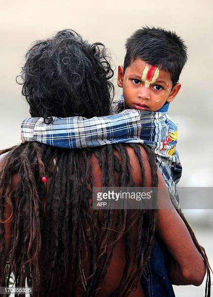 An Indian Hindu Sadhu holds his adopted child Bajrangi while walking on the banks of the Sangam on father's day in Allahabad on June 16 2013 AFP...
