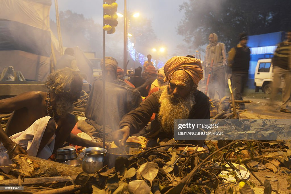 An Indian Hindu Sadhu or holy man prepares his evening meal near a make-shift camp in Kolkata on January 5, 2013. Sadhus form all over the country started to gather in Kolkata on their way to the annual Hindu holy festival Gangasagar Mela, more that hundred thousand Hindu pilgrims will gather at the Gangasagar to take a dip in the ocean at the confluence of the River Ganges and the Bay of Bengal, on the occasion of Makar Sankranti, a holy day of the Hindu calendar considered to be of great religious significance in Hindu mythology. AFP PHOTO/ Dibyangshu SARKAR