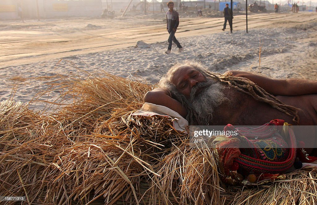 An Indian Hindu Sadhu or holy man rests at the confluence of the Rivers Ganges, Yamuna and mythical Saraswati in Allahabad on December 28, 2012, ahead of The Maha Kumbh Mela. The Kumbh Mela, which is scheduled to take place in the northern Indian city in January and February 2013, is the world's largest gathering of people for a religious purpose and millions of people gather for this auspicious occasion. AFP PHOTO/ Sanjay KANOJIA