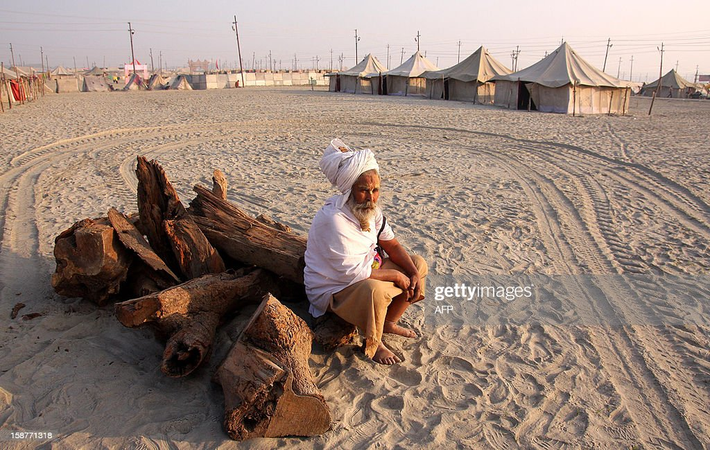 An Indian Hindu Sadhu or holy man rests near tents at the confluence of the Rivers Ganges, Yamuna and mythical Saraswati in Allahabad on December 28, 2012, ahead of The Maha Kumbh Mela. The Kumbh Mela, which is scheduled to take place in the northern Indian city in January and February 2013, is the world's largest gathering of people for a religious purpose and millions of people gather for this auspicious occasion. AFP PHOTO/ Sanjay KANOJIA